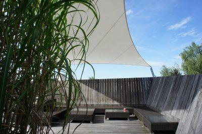 Gemütliche Sitzmöbel unter Sonnensegel mit Jumbogras - so muss Gartengestaltung